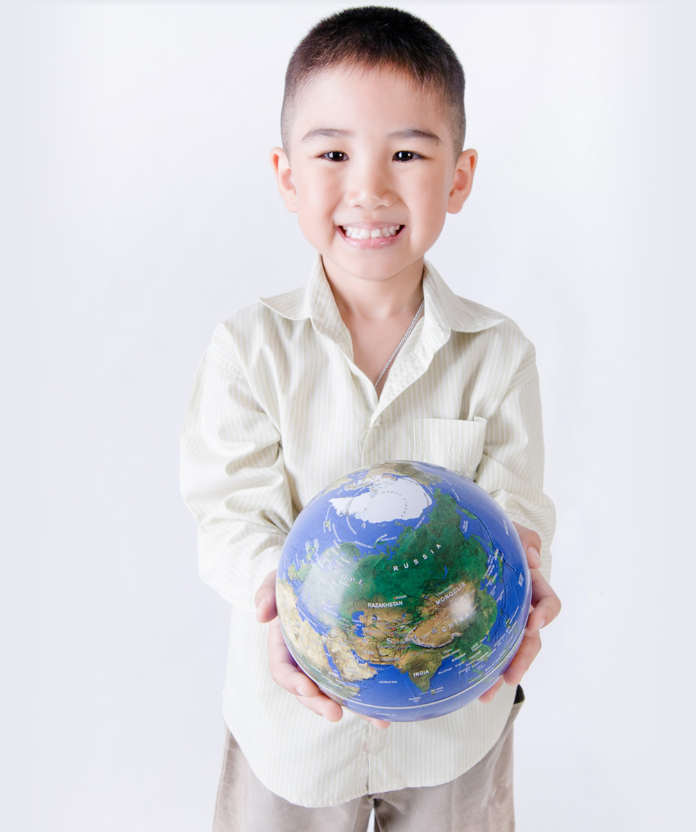 Child holding a globe in his hands.